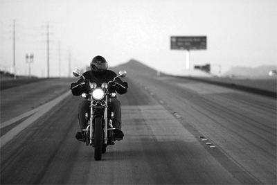 A Lone Biker Riding a Motorcycle In The Wind