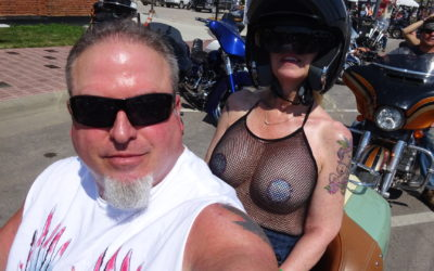 California Motorcycle Accident and Biker Lawyer Norman Gregory Fernandez with wife little Teri on their motorcycle main drag, Sturgis 2019